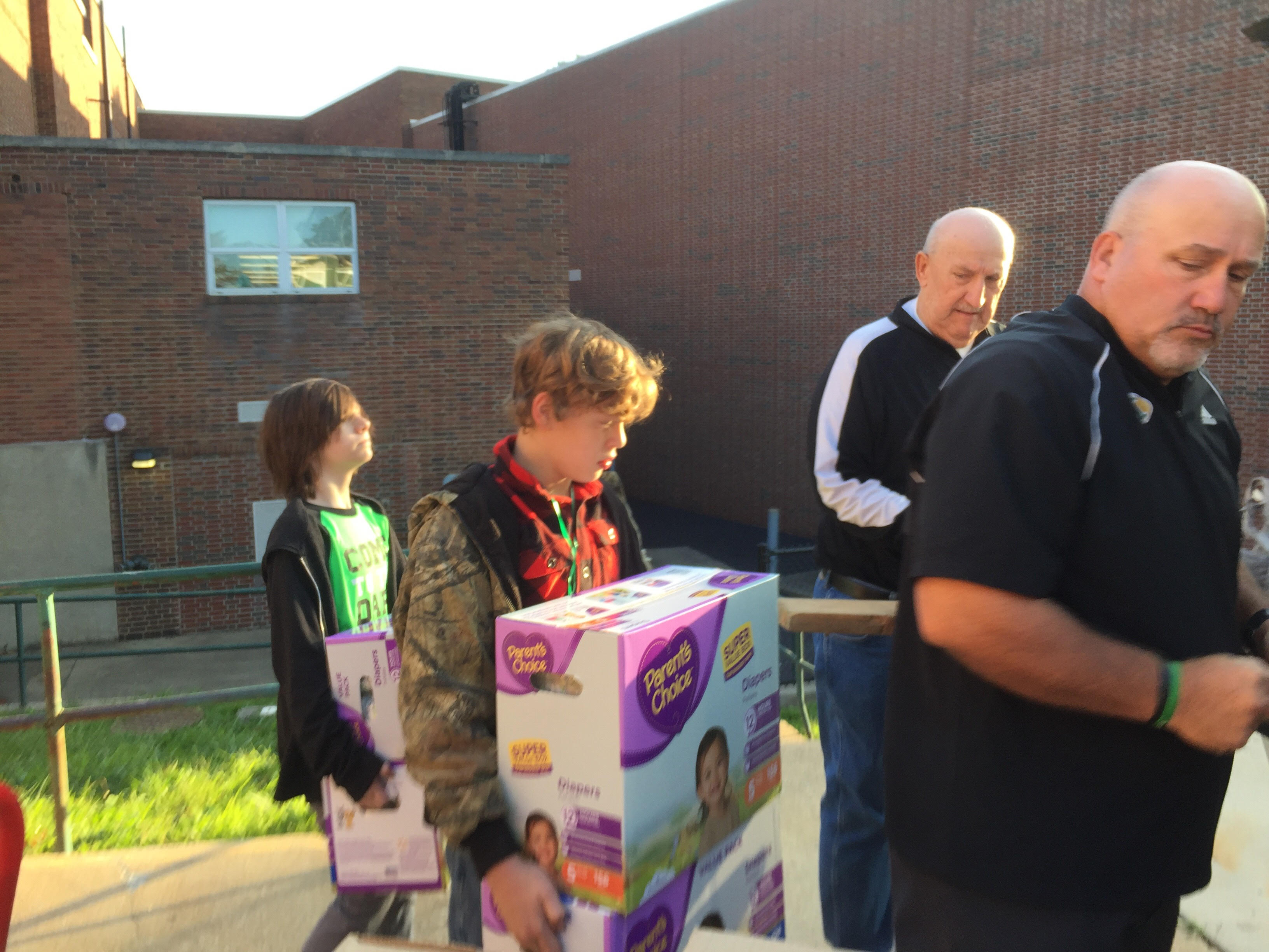Mr. Kostival and Mr. Ricketts help students load the truck